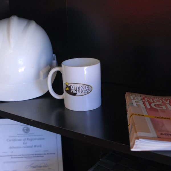 MESS Clean Up office shelf with coffee cup, hardhat and training documents. Serving California's Central Coast with Asbestos, Mold, Lead, and Selective Demolition